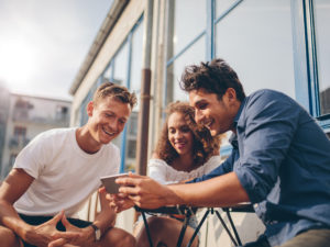 three friends looking at a phone