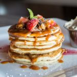 gourmet pancakes topped with berries and syrup