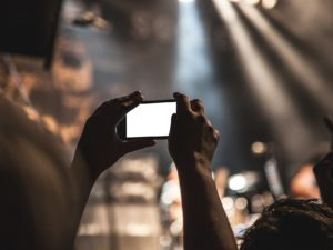 person taking a video at a concert on iphone