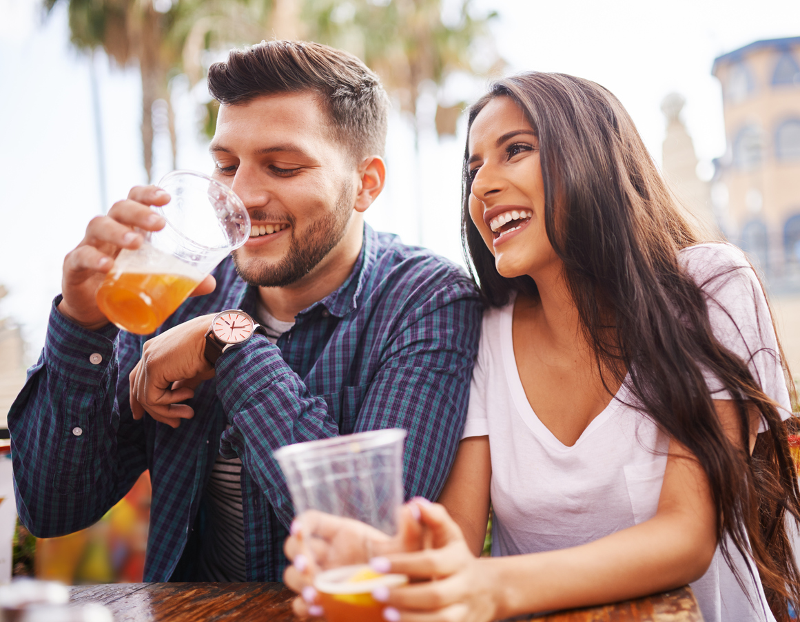 hispanic couple drinking beer on date together at outdoor patio