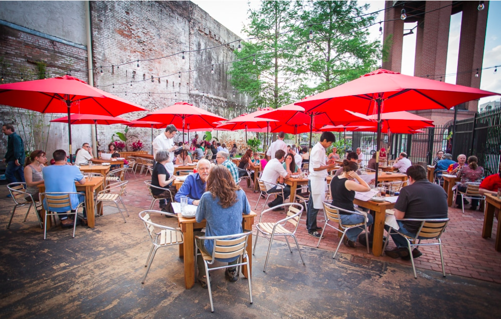 People dining outside at one of the best patios in Houston, TX