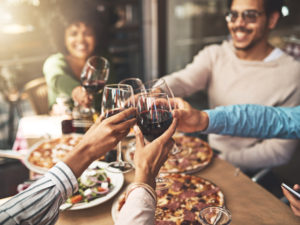 friends cheers over pizza