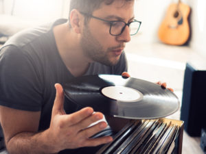young guy cleaning dust from vinyl record