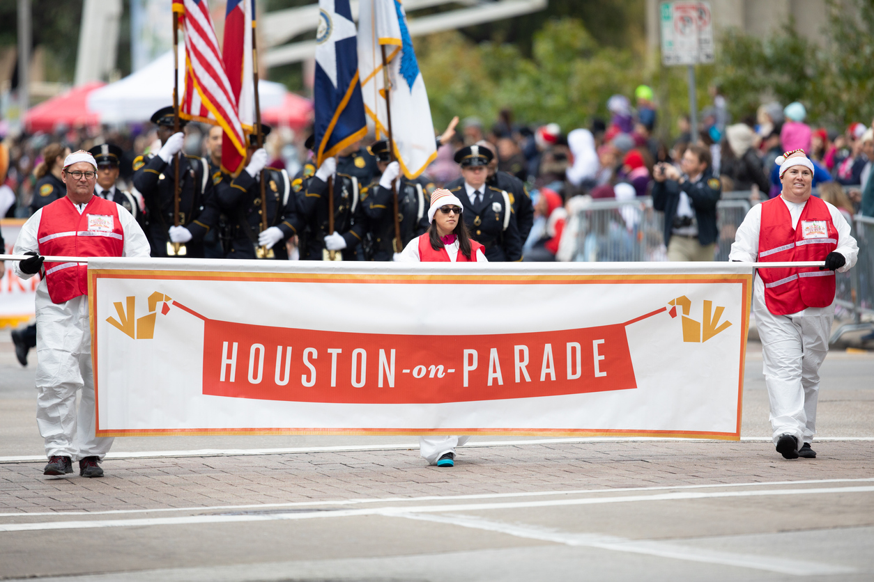 Men and women marching in Houston's Thanksgiving Day Parade.