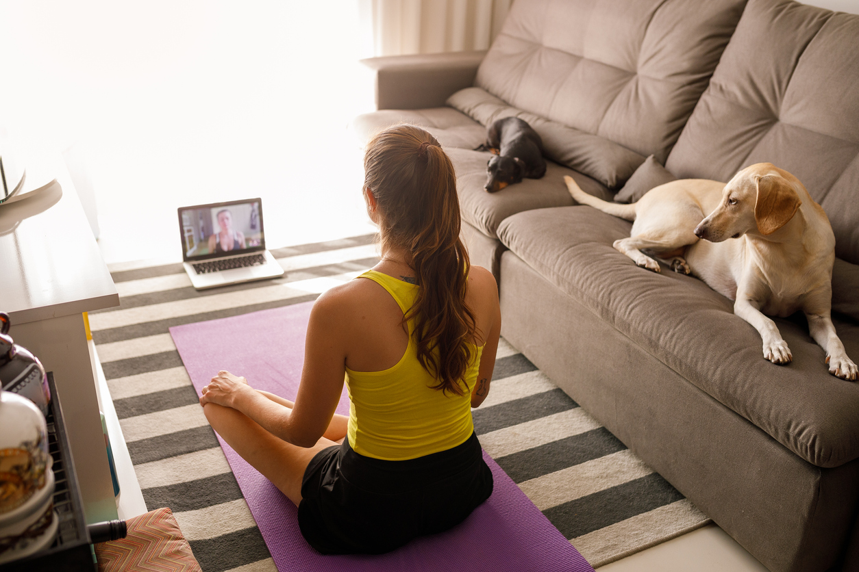 A woman practicing yoga by taking online classes from Houston yoga studios.