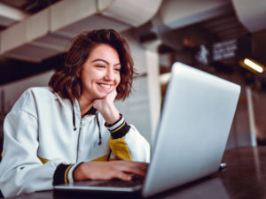 A woman sits in front of a laptop