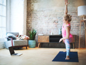 A woman follows along to a yoga class on her laptop in her living room.