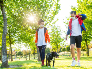 A couple wearing masks walk their dog at a park.
