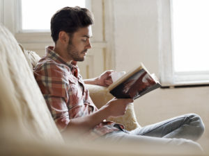 A man sits on a couch with a book and a mug.