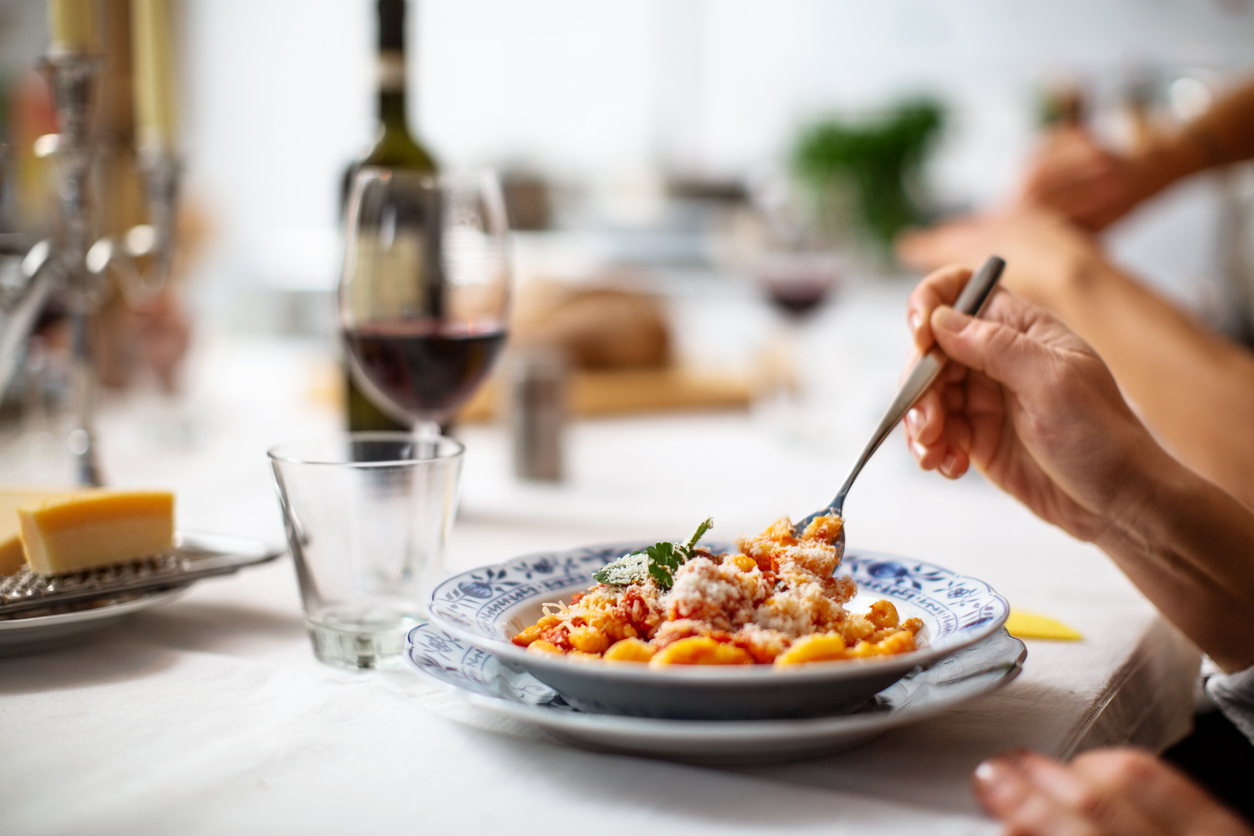 A beautiful pasta dish with a hand twirling a fork - pasta restaurants in Houston