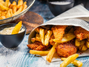 fish and chips wrapped in newspaper, with a dipping sauce | fish and chips to-go in Houston