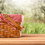 a checkered picnic basket sits on a table in some grass | Houston picnic spots