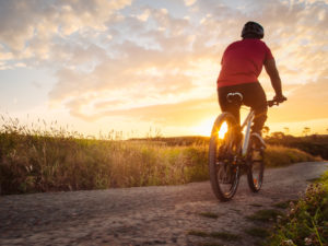 a person riding a bike on a trail at sunset | Houston bike trails